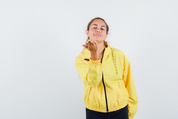 Mulher loira mandando beijos para a frente com jaqueta bomber amarela e calça preta e parecendo séria