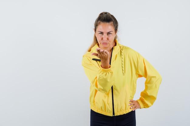 Mulher loira mandando beijos para a frente, segurando a mão na cintura, com uma jaqueta bomber amarela e calça preta e parecendo séria
