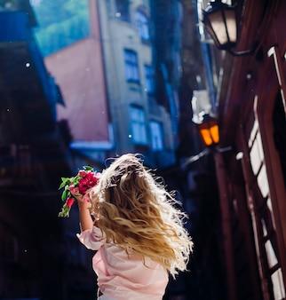 Mulher loira mantém um buquê de peônias cor-de-rosa girando na rua