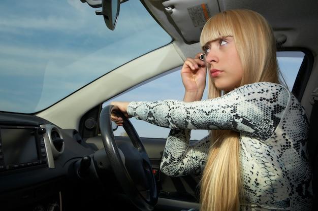 Mulher loira maquiada no carro