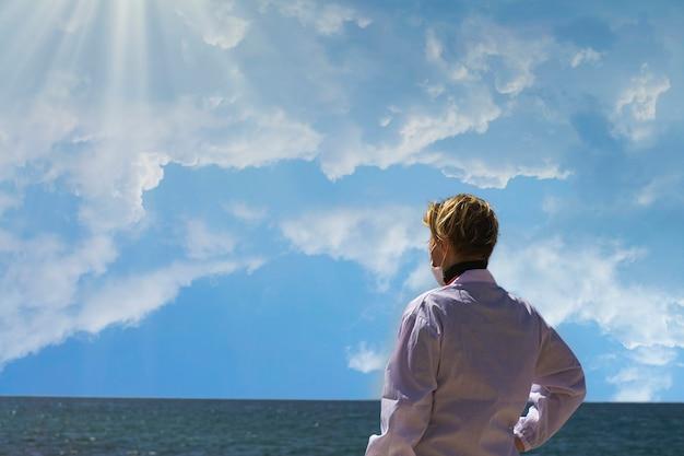 Mulher loira médica de aparência russa caucasiana, olhando para o horizonte azul do mar com esperança. retrato de um profissional médico americano confiante com máscara médica e jaleco branco, de costas para a câmera
