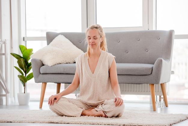 Mulher loira meditando sentada no chão em casa com um sorriso harmônico no rosto