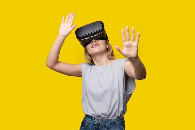 Mulher loira moderna usando um fone de ouvido de realidade virtual e sorrindo em uma parede amarela