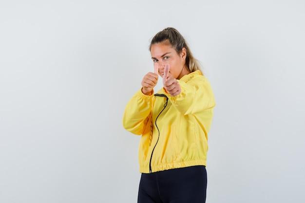 Mulher loira mostrando dois polegares para cima com uma jaqueta militar amarela e calça preta e parecendo feliz