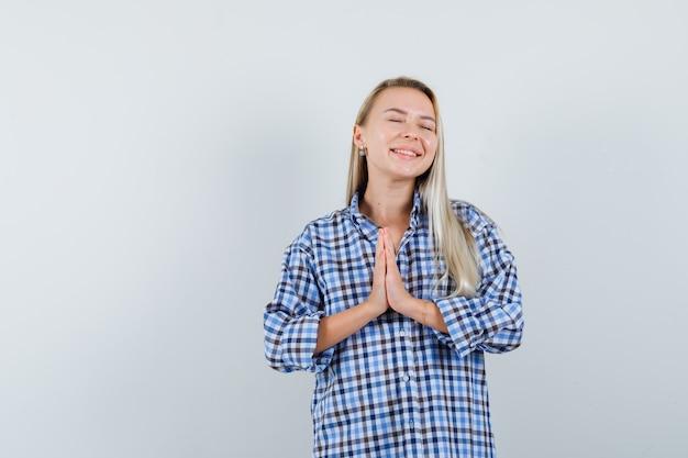 Mulher loira mostrando gesto de namastê em camisa xadrez guingão azul e parecendo radiante. vista frontal.