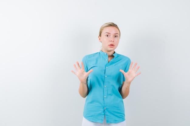 Mulher loira mostrando gesto de pare com blusa azul e parecendo assustada