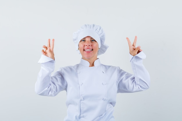 Mulher loira mostrando os sinais da paz com as duas mãos em uniforme de cozinheira branco e bonita