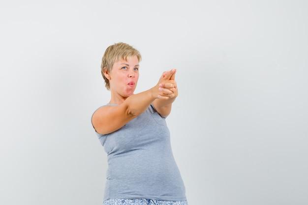 Mulher loira mostrando um gesto de arma para o lado direito em uma camiseta azul clara e olhando com foco. vista frontal.