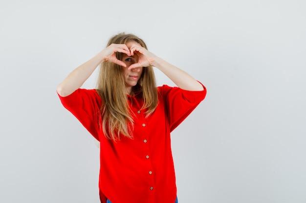 Mulher loira mostrando um gesto de coração na camisa vermelha e olhando otimista.