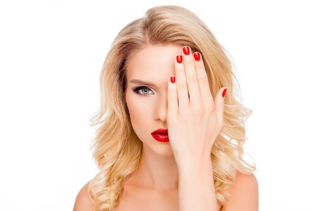 Mulher loira muito elegante escondendo metade do rosto atrás da mão