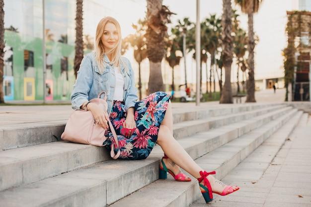 Mulher loira muito sorridente sentada na escada em uma rua da cidade com saia estampada elegante e jaqueta jeans grande e mochila de couro