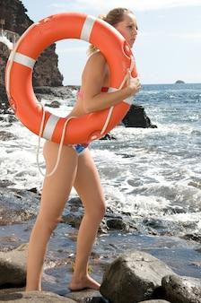 Mulher loira na beira do mar com uma bóia salva-vidas perto das ondas