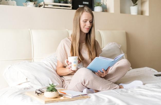 Mulher loira na cama com bloco de notas