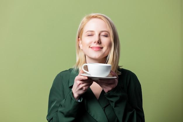 Mulher loira na capa com uma xícara de café