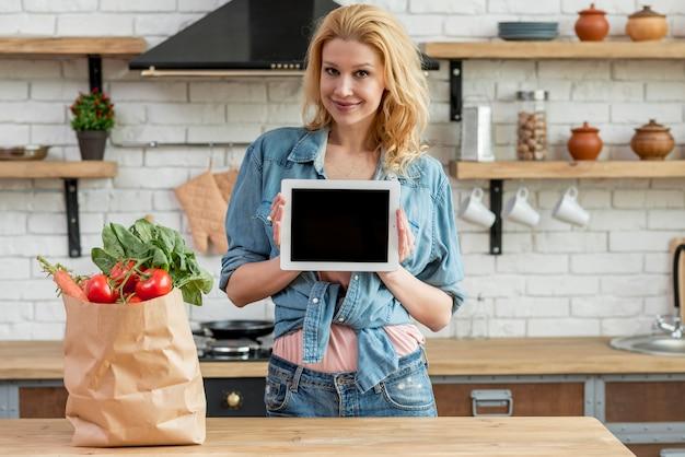 Mulher loira na cozinha com um tablet
