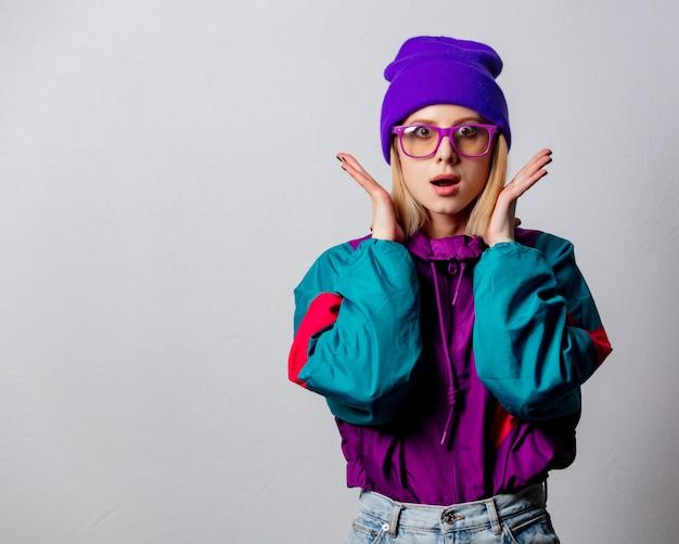 Mulher loira na jaqueta de estilo anos 90 e chapéu com óculos
