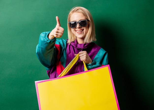 Mulher loira na jaqueta estilo anos 90 com sacolas de compras