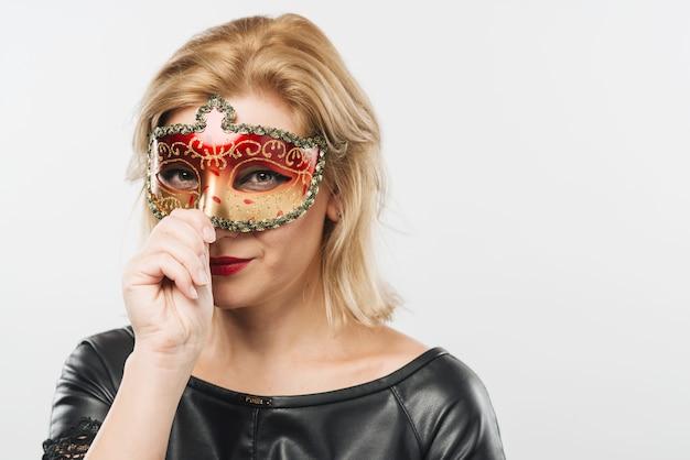 Mulher loira na máscara de carnaval vermelho