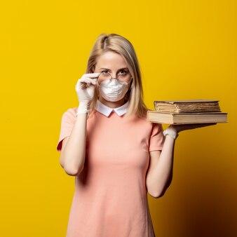Mulher loira na máscara facial e vestido rosa, segurando um livro na parede amarela