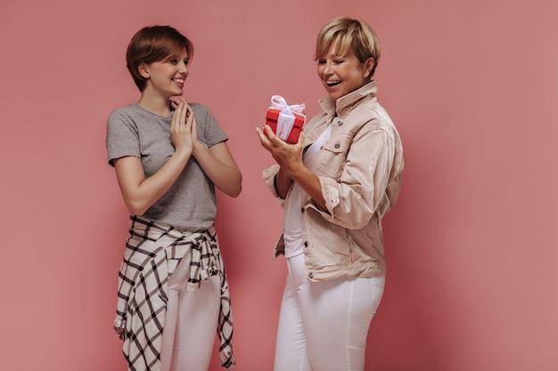 Mulher loira na moda em uma jaqueta bege segurando uma pequena caixa de presente vermelha, sorrindo e posando com jovem em uma camiseta cinza no fundo rosa.
