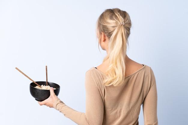 Mulher loira na parede azul isolada na posição traseira, segurando uma tigela de macarrão com pauzinhos