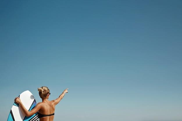 Mulher loira na praia com prancha de surf