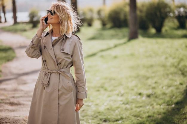 Mulher loira no casaco do lado de fora no parque usando o telefone