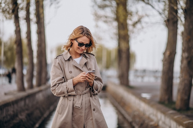 Mulher loira no casaco do lado de fora no parque