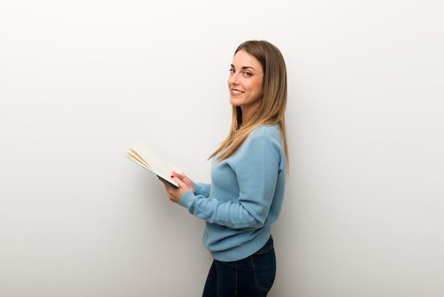 Mulher loira no fundo branco isolado, segurando um livro e gostar de ler
