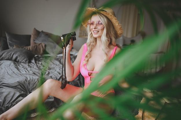 Mulher loira no maiô rosa imitando verão praia férias tempo em casa interior. quarentena divertida. fique em casa, isolamento.