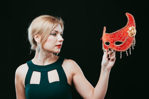 Mulher loira olhando a máscara de carnaval vermelho