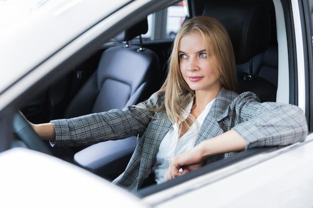 Mulher loira olhando atentamente para a estrada