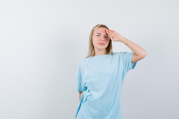Mulher loira olhando para longe com as mãos na cabeça em uma camiseta azul e bonita