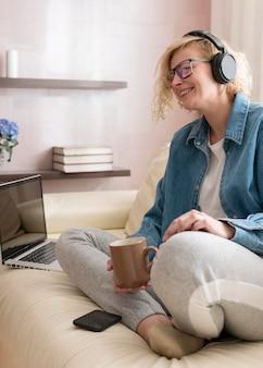 Mulher loira ouvindo música e bebendo café