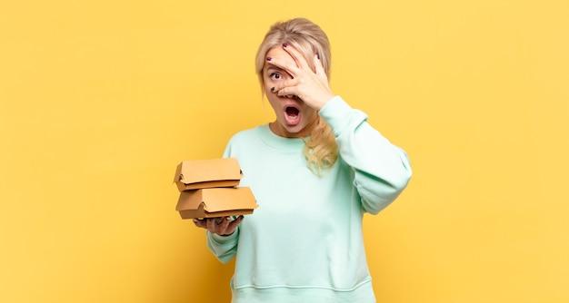 Mulher loira parecendo chocada, assustada ou apavorada, cobrindo o rosto com a mão e espiando por entre os dedos