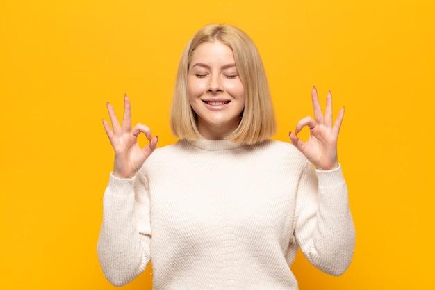 Mulher loira parecendo concentrada e meditando, sentindo-se satisfeita e relaxada, pensando ou fazendo uma escolha