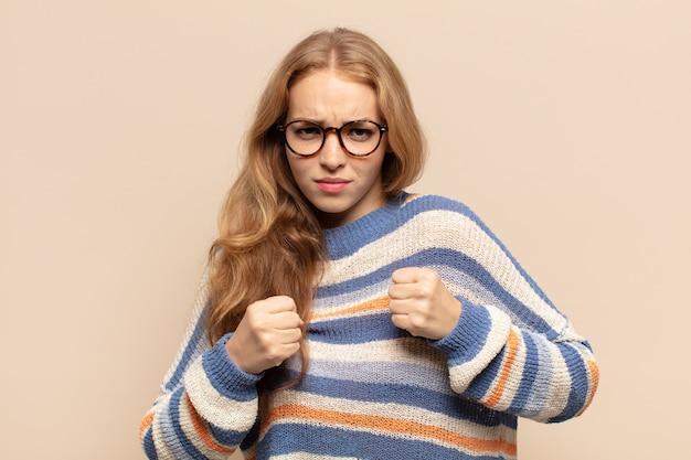 Mulher loira parecendo confiante, zangada, forte e agressiva, com punhos prontos para lutar em posição de boxe
