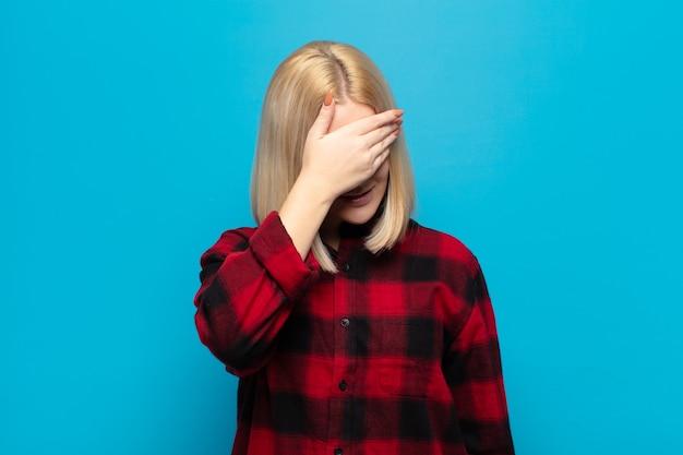 Mulher loira parecendo estressada, envergonhada ou chateada, com dor de cabeça, cobrindo o rosto com a mão