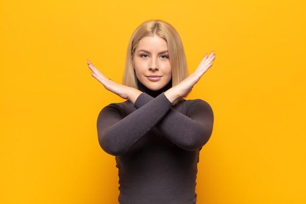 Mulher loira parecendo irritada e cansada de sua atitude, dizendo o suficiente! mãos cruzadas na frente, dizendo para você parar