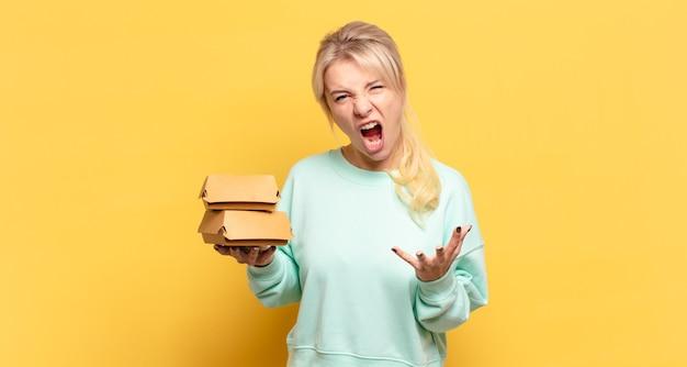 Mulher loira parecendo zangada, irritada e frustrada gritando