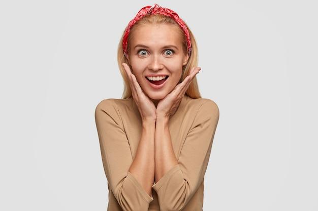Mulher loira pasma positiva mantém ambas as mãos embaixo do queixo, de bom humor ao ouvir algo agradável, vestida com roupa estilosa, tem sorriso largo, mostra dentes brancos até perfeitos, isolada
