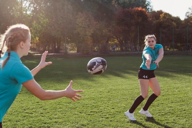 Mulher loira, passando uma bola de futebol