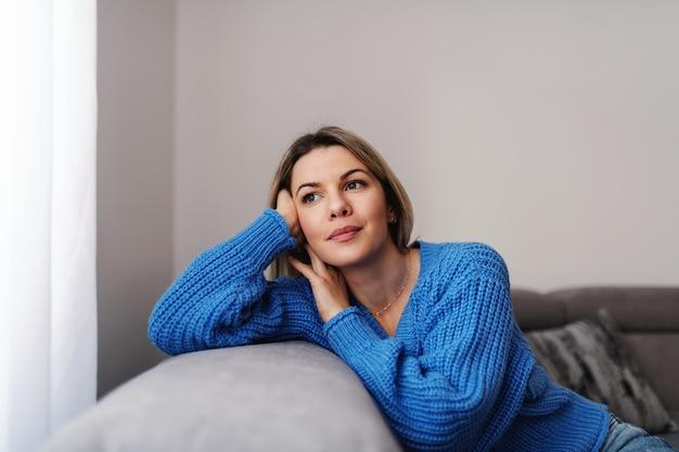 Mulher loira pensativa atraente jovem encostado no sofá e olhando pela janela da calha durante o surto de corona.