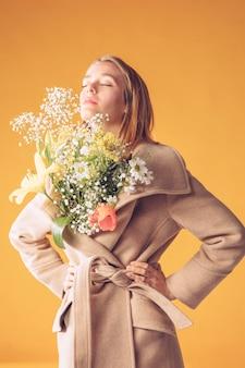 Mulher loira pensativa com buquê de flores no casaco