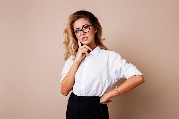 Mulher loira pensativa posando isolado na parede bege. roupa de trabalho casual elegante.