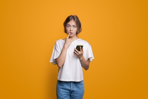 Mulher loira pensativa, segurando um celular e olhando para a câmera, posando na parede amarela do estúdio