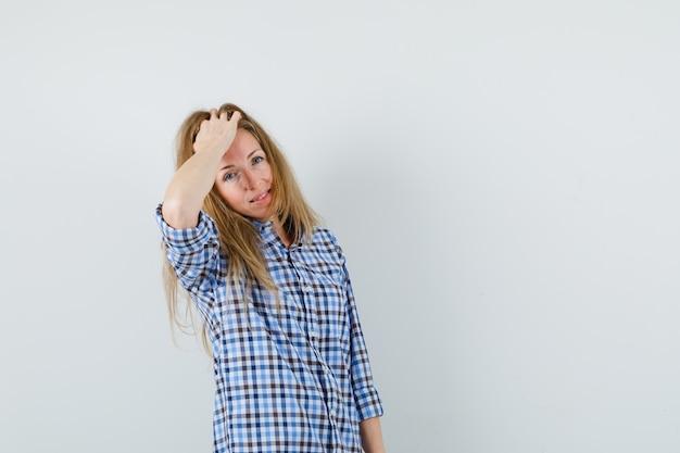 Mulher loira penteando o cabelo com a mão na camisa e parecendo charmosa,
