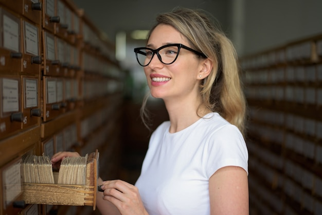 Mulher loira, pesquisando arquivos de livro no catálogo antigo