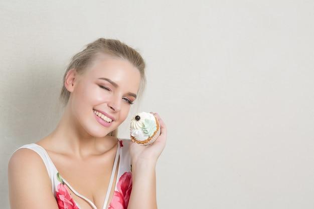 Mulher loira piscando legal com maquiagem perfeita segurando doce sobremesa de creme. espaço para texto