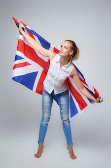Mulher loira. posando com a bandeira do reino unido